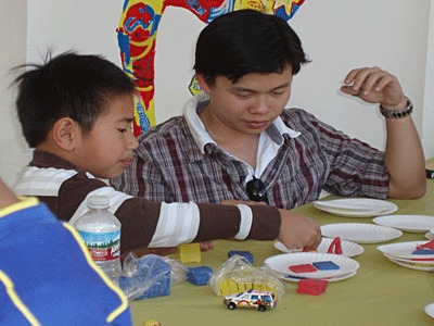 Male college student and young boy working at art table.