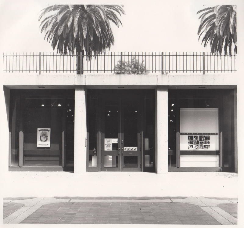 Modernist concrete building, poster in one of three window bays, palm trees behind.