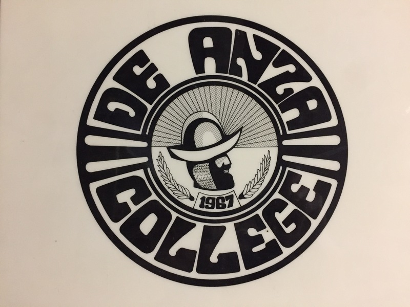 This De Anza College seal, no longer in use, was created by a local high school student and selected as the winner in a design contest. The  profile image in the center is Colonel Don Juan Bautista de Anza.