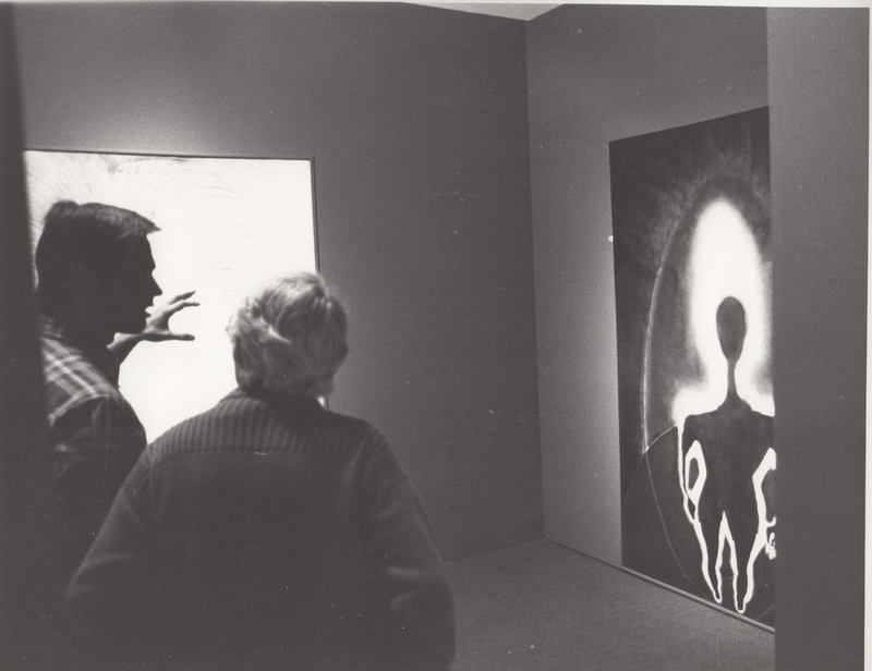 Two gallery viewers look at a painting with a dark body silhouette.
