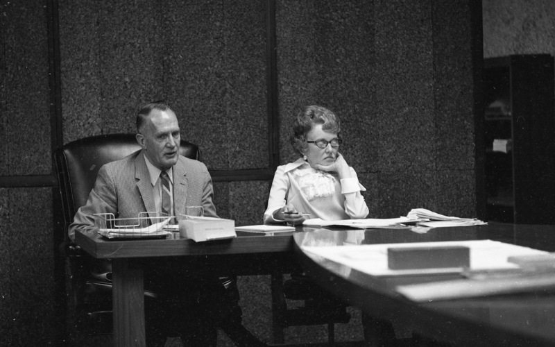 Dr. Calvin C. Flint and his secretary, Lorraine Anderson, attend a meeting of the Board of Trustees in the 1960s.