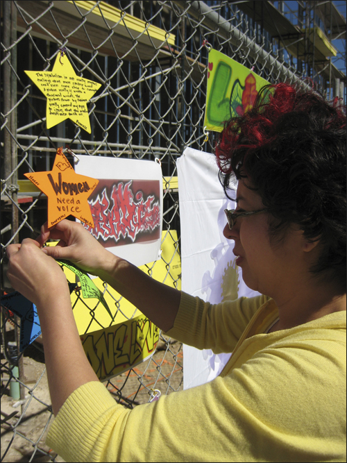 Artist Rodriguez attaches small artwork to chain-link fence surrounding construction site for new Euphrat Museum.