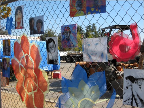 Multiple artworks on chain-link fence at construction site for new Euphrat. Some are large flowers.