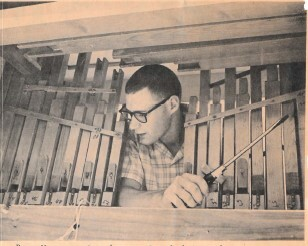 Photograph of Roger Murray examining the inside workings of a barrel organ. Photograph from the June 6, 1961 edition of The (Los Altos) Town Crier.