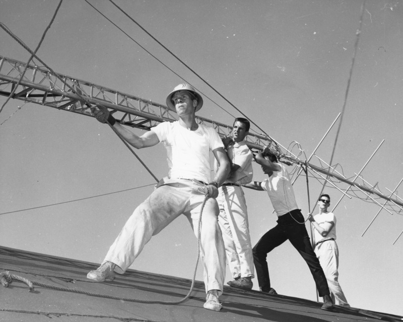 Four men raising the KFJC radio antenna on the roof of the Foothill College building in Mountain View. Pictured from left to right are Bob Ballou, Jim Fernbaugh, Nathan Ballard and Roger Murray. Photographer Gary Pagano for the Foothill Sentinel, October 9, 1959.