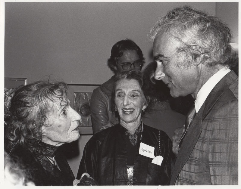 Two artists converse with a male reception guest.
