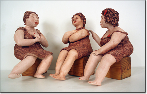 Sculpture of three women casually sitting on boxes, bare feet, talking animatedly.