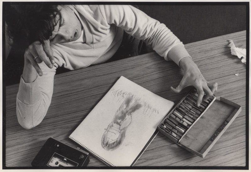 Artist at desk with drawing and art materials.