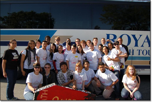 Around 30 students posing in front of a bus.