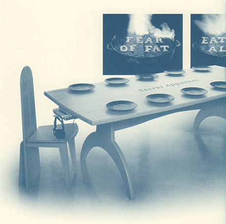 Modernist dining table and chair. Place set with plates, no utensils. 'Fear of fat' on back wall.
