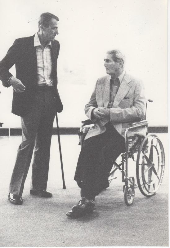 Dr. Diesner, in wheelchair, in conversation with artist with cane.