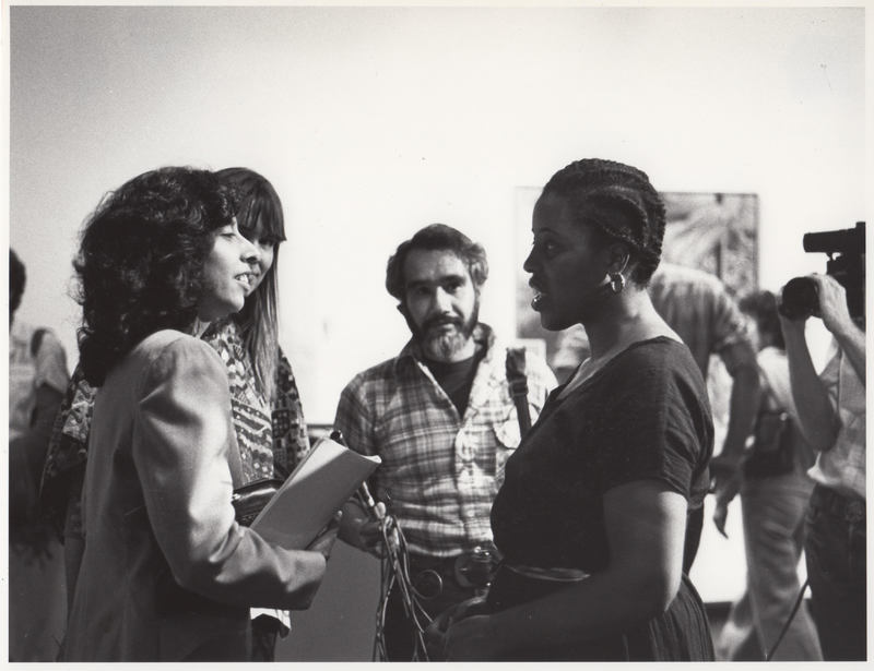 Two women in foreground talk. Male reporter listens. Video camera off to right.