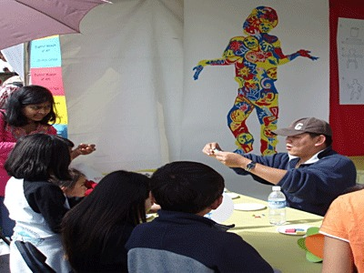 Male college student demonstrating art  to students around an art table.