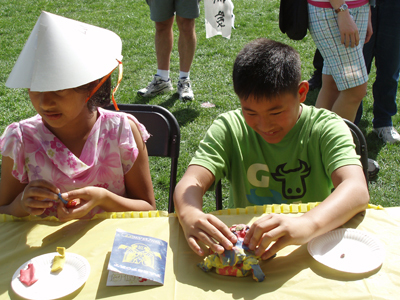 Two students creating art at a table in a sunny outdoor setting.
