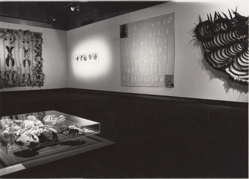 Gallery installation including sculpture and a large feathered cape on one wall.