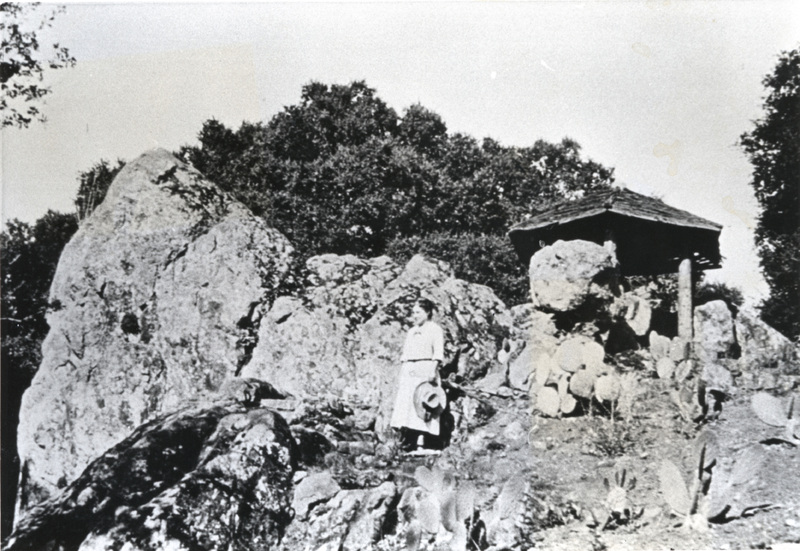 Mrs. Willard M. Griffin stands on the large rocks that now highlight the main entrance to the Foothill College Campus. Behind Mrs. Griffin is a pagoda style structure. The Griffins became enamored of Japanese culture and architecture and used this style of structure on many areas of their land.