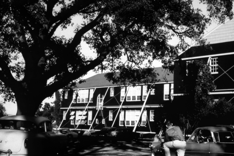A student leans on a car in front of the Highway School on El Camino Real in Mountain View, California. This school was the temporary location of Foothill College from 1958-1961. The permanent campus on El Monte Road in Los Altos Hills opened to students in September of 1961.