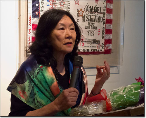 Connie Young Yu speaking in front of a Flo Oy Wong artwork.