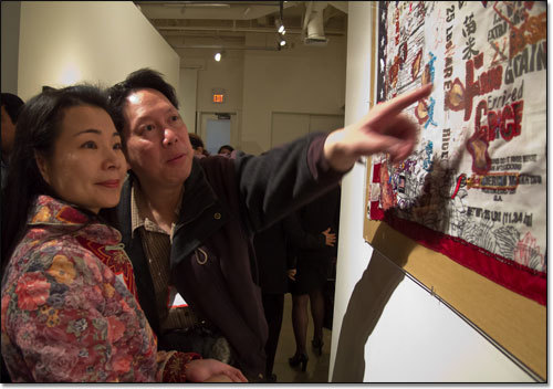 Two museum visitors , one pointing at a detail of Flo Oy Wong's art.