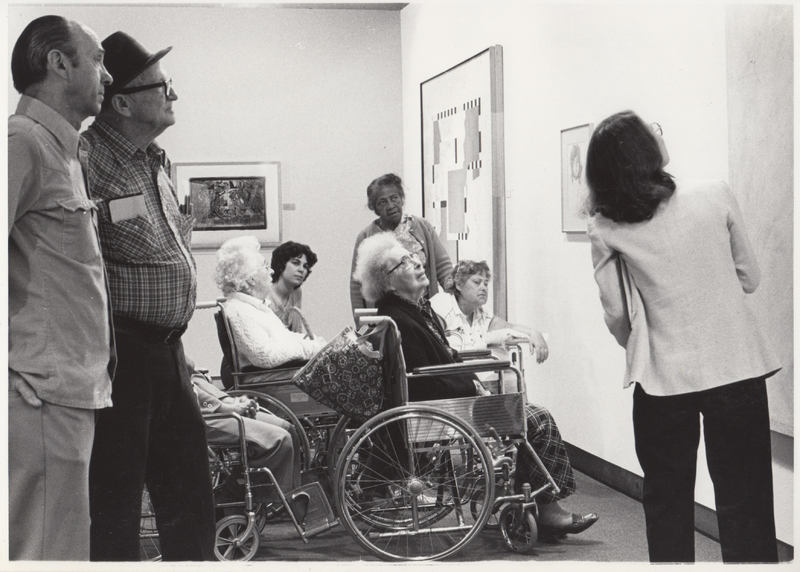 Docent gives exhibition tour to seniors, several using wheelchairs.