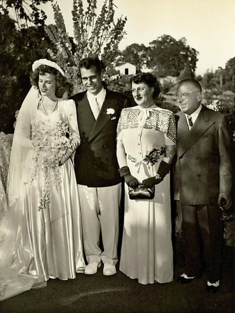 Wedding photo of the young couple with his parents.