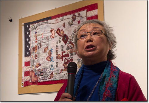 Flo Oy Wong speaking in front of one of her artworks.