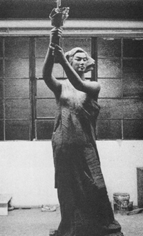 Photo of sculpture of woman holding torch. Background is empty warehouse.