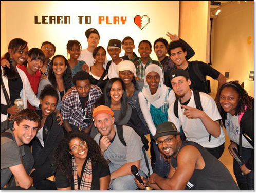 Group photo of First Thursday performers in front of Learn to Play wall sign with its half white, half red heart logo.
