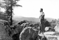 Calvin C. Flint stands atop the large rock outcropping and views the future site of Foothill College in 1958. These rocks still stand on the Foothill campus, marking the entrance to the college.