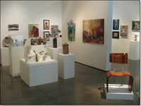 Multiple small sculptures on pedestals, multiple paintings on walls.