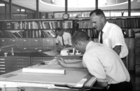 Dr. Calvin C. Flint reviews architectural drawings of Foothill College in the offices of Ernest P. Kump in Palo Alto, California.
