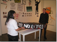 Two activist students installing a coffin-like sculpture with 'Education' written on it.