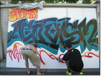 Two activist students spray painting a mural that says 'Activism.'