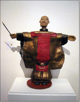 Warrior sculpture with hands outstretched to sides, holding a baton.